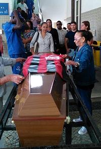 Josefa, a Josê, estende a bandeira do Flamengo no caixão de Bartô. Foto: Marcelo Auler
